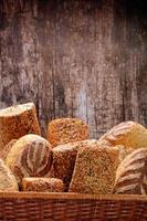 pão granulado saudável na cesta de vime em fundo de madeira foto