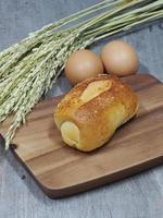 pão fresco e trigo na madeira foto