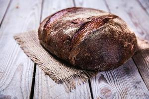 comida, bom pão de centeio em um fundo de madeira foto