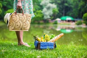 cesta de piquenique com frutas, pão e chapéu no saco de palha foto