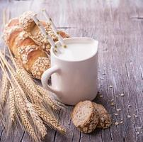 jarro com leite no café da manhã e baguetes de pão caseiro fresco foto