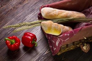 paprika e cesta de pão no fundo de madeira. foto