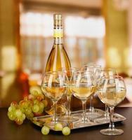 vinho branco em vidro e garrafa no fundo da sala