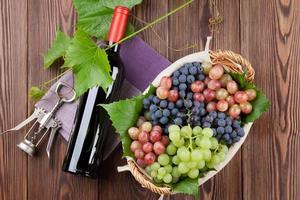 garrafa de vinho tinto e uvas coloridas