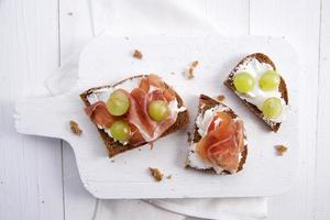 pão, queijo, presunto e uvas foto