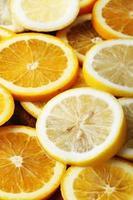 pilha de fatias de frutas cítricas. laranjas e limões. foto