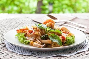 espaguete de frutos do mar em prato branco foto