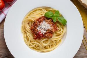 espaguete com molho à bolonhesa parmesão e manjericão foto