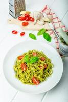 tagliatelle de espinafre com pesto de manjericão e mini tomate foto