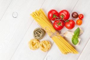 macarrão, tomate, manjericão na mesa de madeira foto