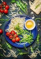 massa italiana em tigela com tomates e ingredientes para cozinhar foto