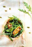 salada com rúcula, tomate seco e gergelim em toranja
