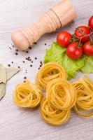 macarrão, tomate e pimenta em um fundo de madeira foto