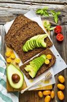 sanduíche com pão de centeio na mesa de madeira velha. com abacate foto