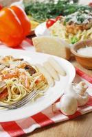 macarrão com camarões e mashrooms na mesa de madeira