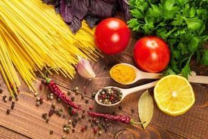 macarrão cru, legumes, manjericão e especiarias na mesa de madeira foto