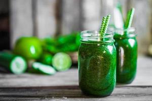 smoothie verde sobre fundo de madeira rústico foto