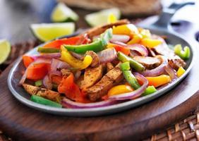 fajitas de frango mexicano em frigideira de ferro com pimentos foto