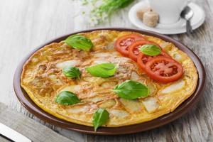 omelete de batata com tomate em um prato foto