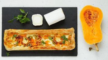 torta com abóbora, queijo de cabra, azeitonas na placa de pedra foto