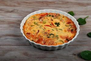 quiche fresco sem crosta com legumes. refeição em família. foto