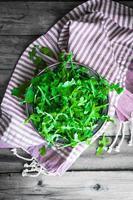 salada de rúcula em fundo de madeira foto
