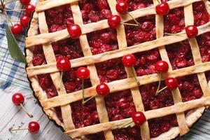 torta de cereja e frutos maduros close-up vista superior horizontal foto