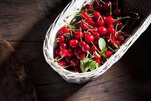 cerejas ácidas na cesta na madeira foto