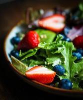 salada verde com frutas no fundo de madeira foto