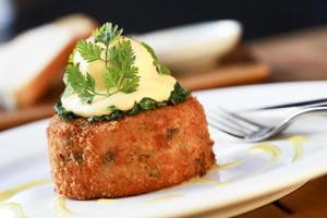 um bolo de peixe com ovo escalfado e espinafre por cima foto