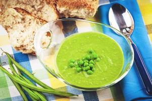 sopa de ervilha verde em uma tigela com pão e creme de leite