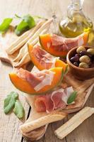 melão cantalupo com azeitonas prosciutto grissini. appeti italiano