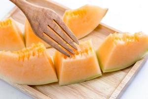melão cantalupo suculento com garfo em uma placa de madeira foto