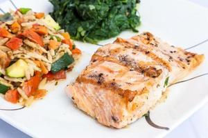 delicioso salmão grelhado com acompanhamentos foto