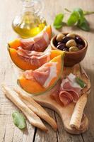 melão cantalupo com azeitonas prosciutto grissini. appeti italiano foto