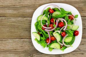 salada de jardim no prato com fundo de madeira foto