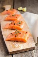 bifes de salmão cru na placa de madeira