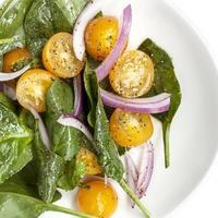 salada de espinafre com tomate cereja amarelo e cebola vermelha foto