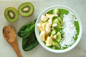 tigela de smoothie verde com colher em mármore branco foto