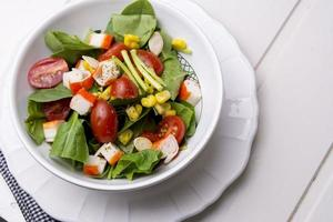 salada de espinafre com tomate cereja e milho em uma tigela foto
