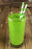 smoothie verde sobre fundo rústico de madeira foto