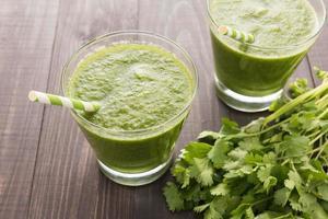 vegetais verdes saudáveis e smoothie da fruta verde em madeira rústica foto