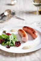 salsichas grelhadas com salada em um prato branco