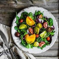salada fresca com espinafre, rúcula e tomate da herança em rústico foto