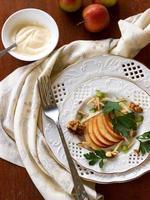 salada com maçãs, nozes e aipo no prato foto