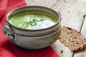 sopa de legumes verde em uma tigela de cerâmica em madeira rústica foto