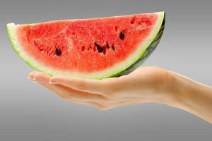 mão feminina com melancia foto