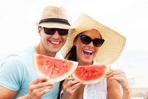 casal segurando fatias de melancia