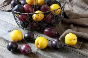 ameixas frescas na cesta na placa de madeira foto