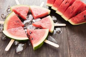 sorvete de frutas fatiadas de melancia em fundo de madeira foto